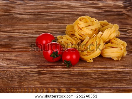 pasta on wooden background with tomato top view