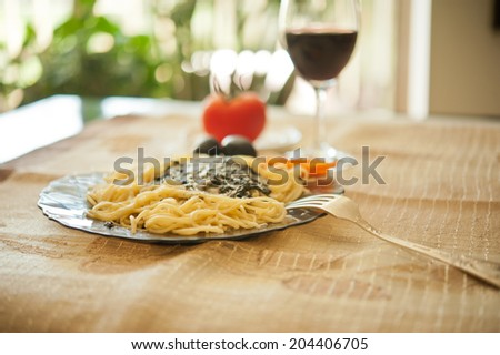 Pasta Pasta Pasta with sauce, parmesan cheese, black olives and spicy peppered carrots and a glass of wine - stock photo