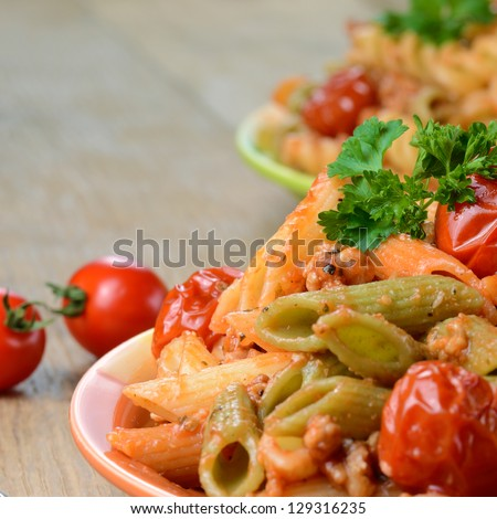 Pasta penne with bolognese tomato beef sauce on the kitchen table
