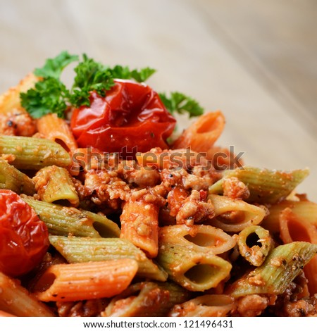 Pasta penne with bolognese tomato beef sauce on the kitchen table with copy-space