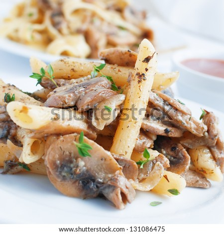 pasta penne with mushrooms grilled in sour cream sauce - stock photo