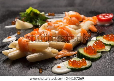 Pasta penne with salmon, caviar and fresh onion - stock photo