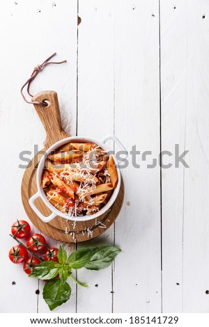 Pasta Penne with tomato sauce on white wooden background - stock photo