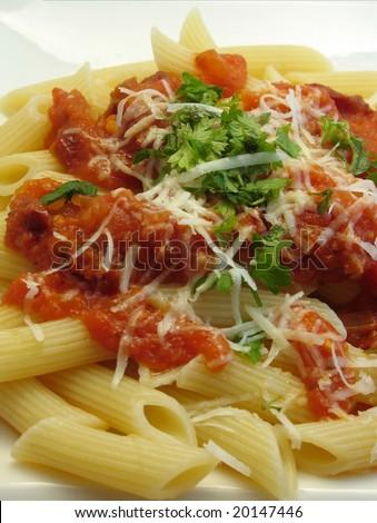 Pasta, penne, with tomato sauce, parmesan and fresh herbs on a white plate - stock photo