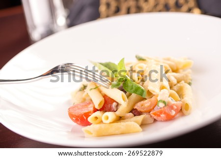 Pasta penne with tomatoes and basil leaf on the table at restaurant - stock photo