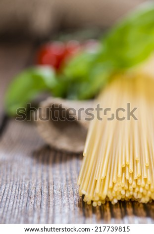 Pasta (raw Spaghetti) on an old wooden table (close-up shot) - stock photo