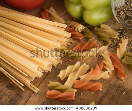 Pasta raw, spaghetti on wooden background