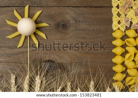 Pasta's flower with wheat on wooden background. - stock photo