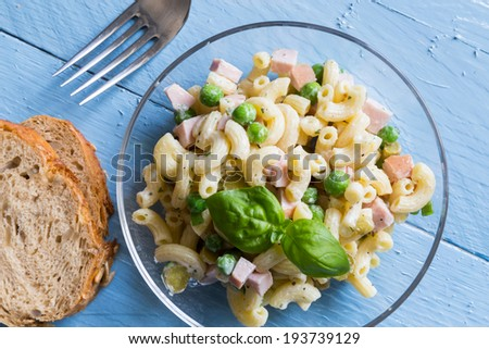 Pasta salad in a glass bowl on blue wood. - stock photo