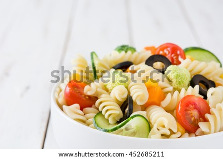 Pasta salad in bowl on white wooden table