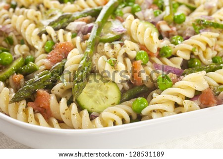 Pasta salad made with asparagus, peas, red onion, cucumber and scraps of left over smoked salmon. - stock photo