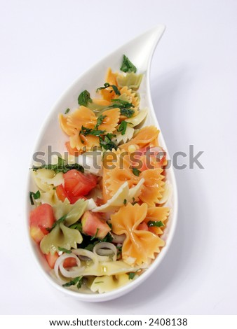 pasta salad on white bowl with stone decoration