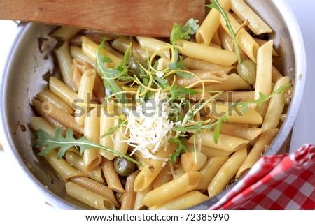 Pasta salad sprinkled with arugula, lemon zest and Parmesan - stock photo