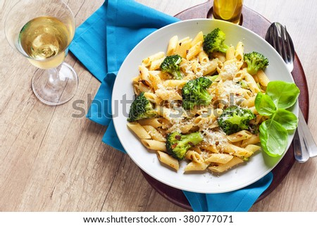 pasta salad with broccoli and Parmesan cheese. with white wine .on a wooden table. Healthy Italian food - stock photo