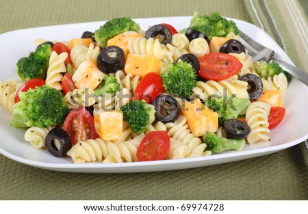 Pasta salad with cheese, tomatoes, black olives and broccoli - stock photo