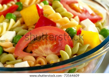 Pasta salad with fresh vegetables (tomato, pea, bell pepper, cucumber) in glass bowl (Selective Focus, Focus on the tomato slice) - stock photo