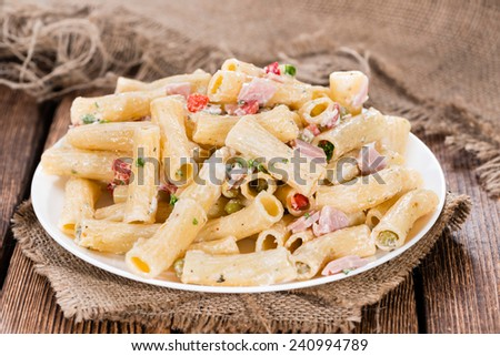 Pasta Salad with ham and mayonnaise on wooden background - stock photo