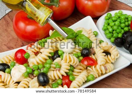Pasta salad with mozzarella and basil - stock photo