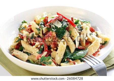 Pasta salad with spinach leaves, bell peppers, sundried tomatoes, and parmesan cheese.  Healthy fresh eating.