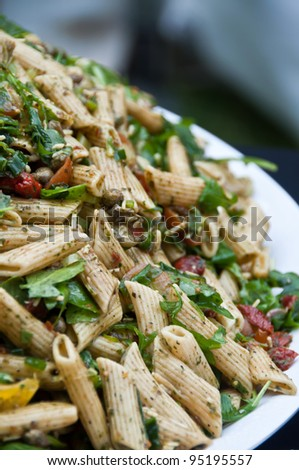 Pasta salad with sun dried tomatoes and spinach - stock photo