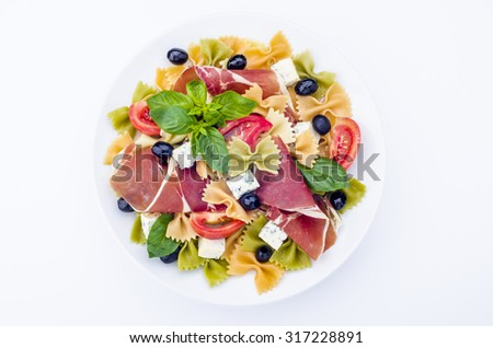 Pasta salad with tomato,  ham, olive and blue cheese - stock photo