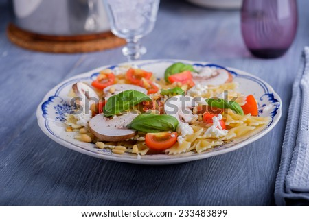 Pasta salad with tomatoes and mushrooms and some basil - stock photo