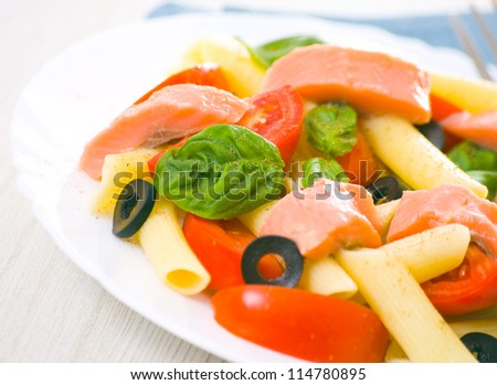 Pasta salad with tomatoes, basil leaves and fish