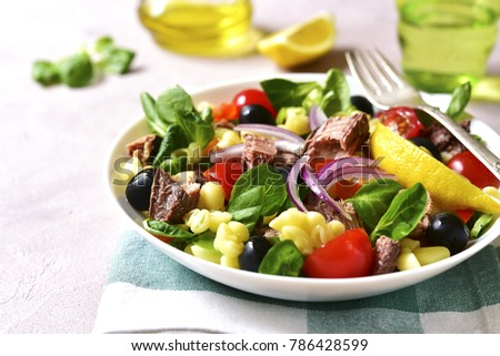Pasta salad with tuna and vegetables in a white bowl on a light concrete or stone background.