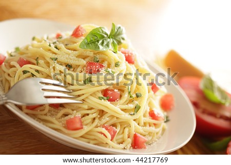 Pasta serving with tomatoes, cheese and basil leaves with a digging in fork