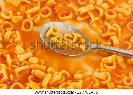 Pasta shaped letters spelling the word PASTA on a spoon within pasta shaped letters in tomato sauce