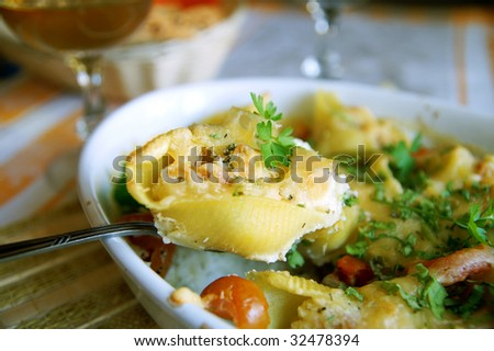 Pasta shells filled with crab meat, and white sauce - a dish of Mediterranean cuisine, blur background, closeup - stock photo