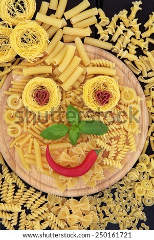 Pasta smiley face abstract background on a wooden board. - stock photo