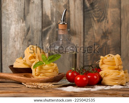 Pasta spaghetti, vegetables and spices, on wooden table, on balck stone background