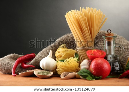 Pasta spaghetti, vegetables and spices, on wooden table, on grey background - stock photo