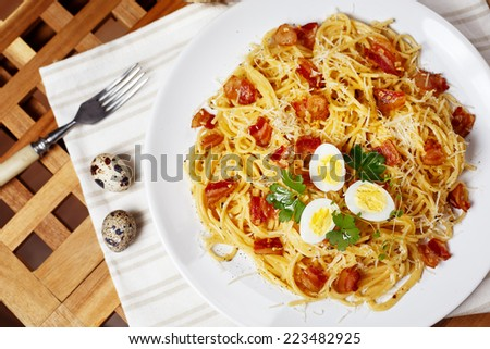 Pasta. Spaghetti with carbonara sauce, parmesan cheese, bacon and quail eggs on wooden table. Italian cuisine. Mediterranean food. Top view. - stock photo