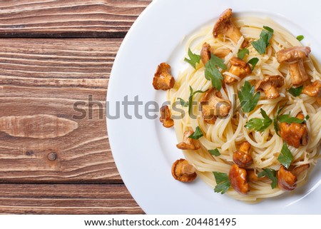 Pasta spaghetti with chanterelles mushrooms closeup on wooden background top view horizontal   - stock photo
