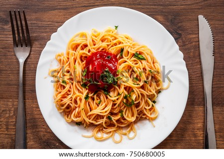 Pasta spaghetti with tomato sauce on white plate. on a wooden background. top view
