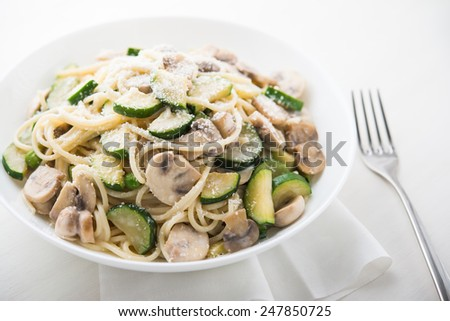 Pasta ( spaghetti ) with zucchini, mushrooms, creamy sauce and parmesan. - stock photo
