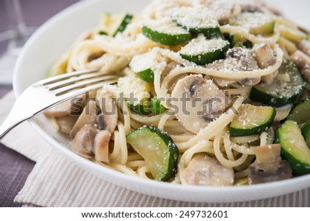 Pasta ( spaghetti ) with zucchini, mushrooms, creamy sauce and parmesan close up. - stock photo