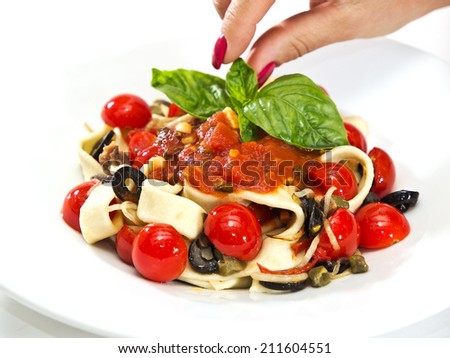Pasta tagliatelle with sauce, basil, olive and cherry tomato