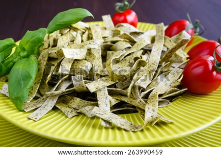 Pasta tagliatelle with spinach basil and cherry tomatoes on light green dish - stock photo