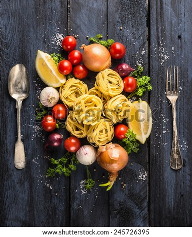 pasta tagliatelle with tomatoes, vegetables and spices for tomato sauce,spoon and fork on dark blue wooden background, top view - stock photo