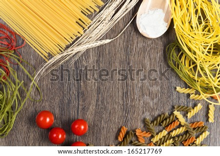 pasta, tomatoes and flour on the spoon, still life - stock photo
