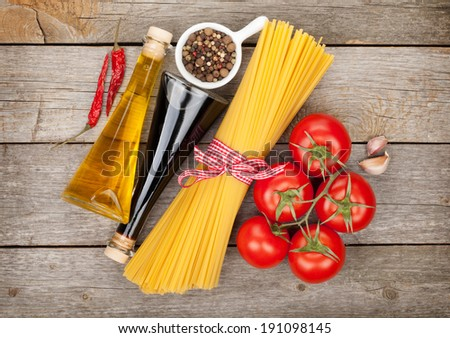 Pasta, tomatoes, condiments and spices on wooden table background - stock photo