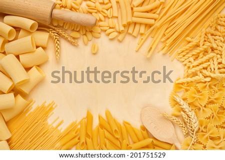 pasta types and kitchen utensils on wooden table - stock photo