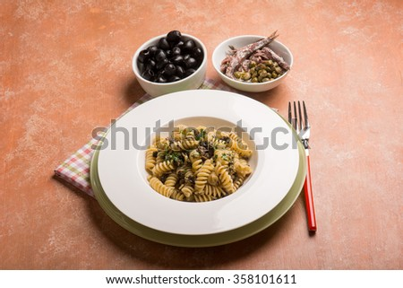 pasta with anchovies capers and black olives - stock photo