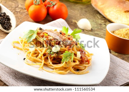 Pasta with anchovies, tomatoes, garlic and breadcrumbs on complex background