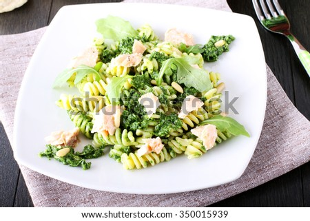 Pasta with arugula pesto and salmon on complex background - stock photo