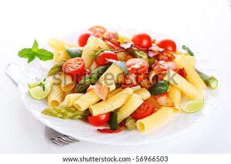 Pasta with asparagus, tomatoes and bacon on a white background - stock photo