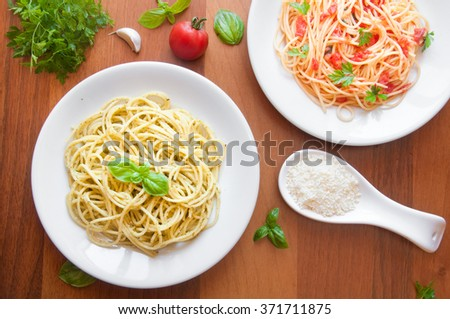 Pasta with basil and tomatoes on wooden table - stock photo
